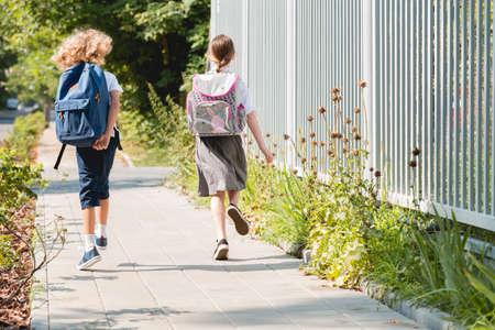 Dos niños con mochilas volviendo a casa juntos. Foto de archivo
