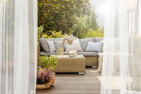 Nowocześnie zaprojektowany przytulny ganek z rattanowymi meblami i drewnianą podłogą