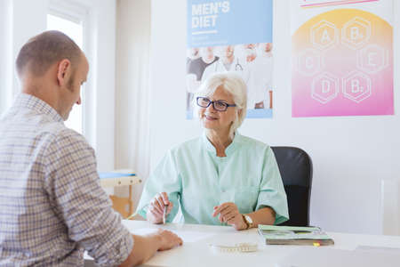 Dietician and her patient planning his diet together Stock Photo