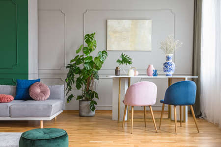 Velvet pastel pink and petrol blue chairs at small dining table in bright living room