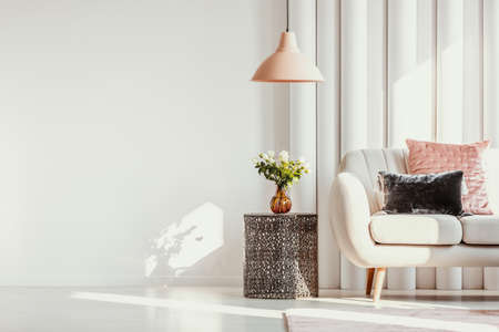 Copy space on white wall of elegant living room with white flowers on glass vase on stylish table next to white sofa with pastel pink and black velvet pillows