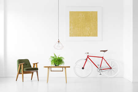 Dark green vintage armchair next to wooden coffee table with plant and red bike in living room interior with yellow painting on white wall