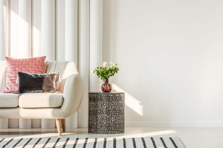 White flowers on glass vase on stylish table next to white sofa with pastel pink and black velvet pillows, real photo with copy space on empty white wall