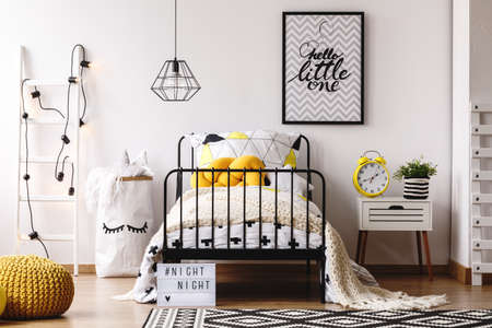 Yellow knot pillow on single metal bed in bright bedroom interior with white scandinavian ladder, paper bag with toys and nightstand with yellow clock and green plant in striped pot Foto de archivo