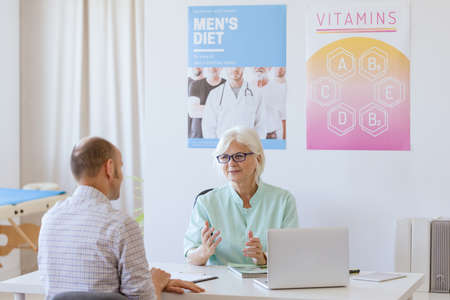 Older dietician talking to male patient about his diet