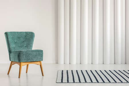 Stylish turquoise armchair in empty white interior with striped rug