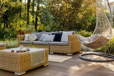 Cozy porch with wooden floor, rattan furniture and hanging chair