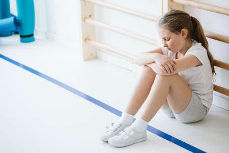 Chica desmotivada sentada sola en un gimnasio durante las clases