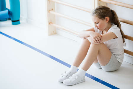 Demotivated girl sitting alone in a gym hall during classes