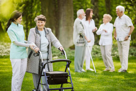 Group of senior patients with caregiver in the garden of nursing home Reklamní fotografie