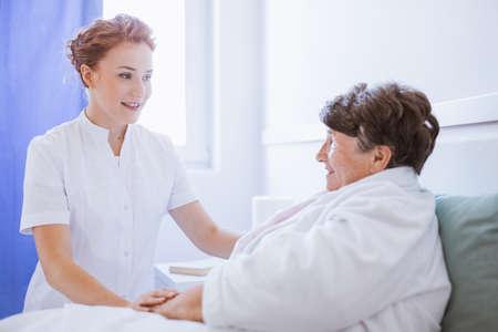 Joven cuidador pasar tiempo con un paciente enfermo en un hogar de ancianos