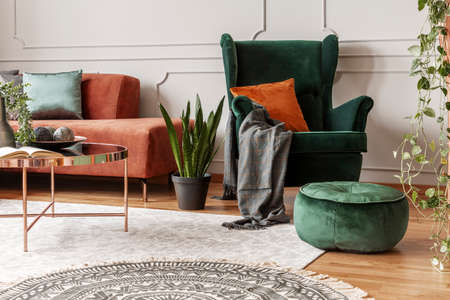 Brown velvet corner sofa and emerald green wing back chair in classy living room