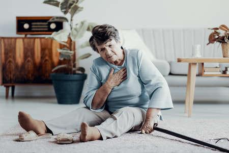 Schwache ältere Frau mit Herzinfarkt, die allein zu Hause mit Gehstock sitzt