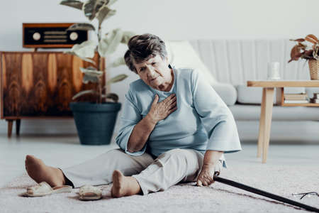 Weak senior woman with heart attack sitting alone at home with walking stick Stock Photo