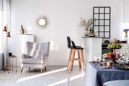 Trendiger grauer Sessel neben zwei schwarzen Barhockern aus Holz in modischer Küche und Esszimmer Standard-Bild