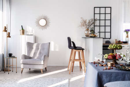 Trendy grey armchair next to two black wooden bar stools in fashionable kitchen and dining room interior Imagens