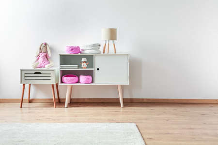 Small toy in pink clothes on white wooden nightstand table next to white cabinet with in elegant interior Banco de Imagens