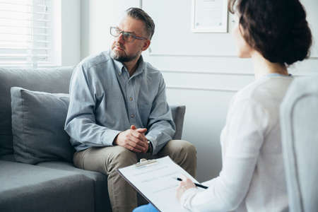Psychotherapist working with adult man in office