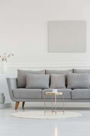 Small elegant coffee table in front of long scandinavian couch in bright daily room interior