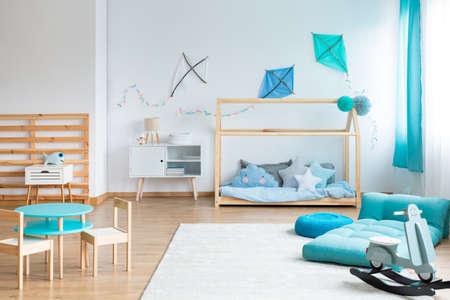 Hágalo usted mismo cometas azules en la pared blanca vacía en el dormitorio escandinavo para niños