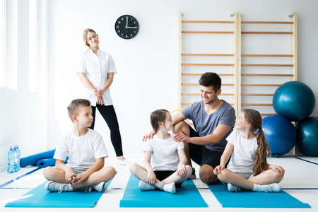 Young kids on physical exercises with two therapists