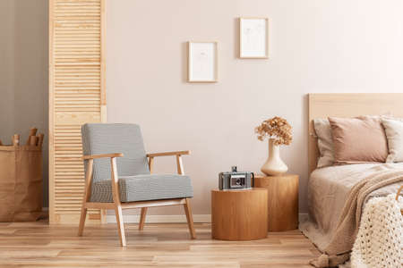 Beige kid's room with wooden nightstand with flowers vintage camera, single bed and retro armchair Banco de Imagens