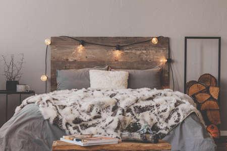 Couette chaude sur lit confortable avec tête de lit rustique avec lumières Banque d'images