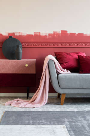 Pink Blanket And Burgundy Pillows On Grey Sofa In Trendy Living
