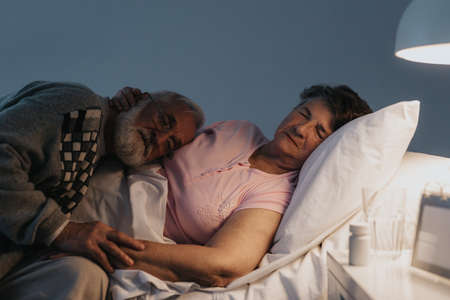 Older man sleeping with terminally ill wife in the hospital