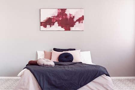 Pintura abstracta de amaranto y rosa pastel sobre una cama king size con ropa de cama rosa y negra Foto de archivo
