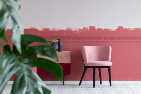 Stylish small pastel pink chair next to trendy pink and burgundy commode 写真素材