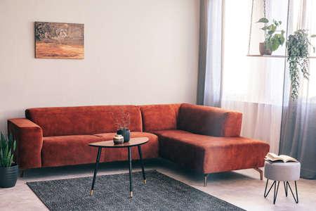 Echtes Foto eines roten Wildledersofas, das in der Ecke eines hellen Wohnzimmers mit Pflanzen auf einer Schaukel steht