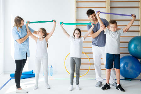 Group of kids exercising with therapist during physical therapy