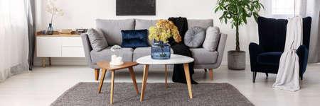 Fleurs sur une table basse en bois dans un intérieur de salon à la mode au design scandinave