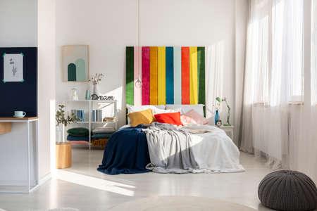 Interno colorato della camera da letto con testiera color arcobaleno
