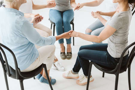 Group of women holding their hands and mediating together 写真素材