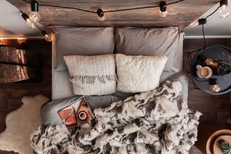 Top view of unmade bed with pillows, warm blanket and magazine