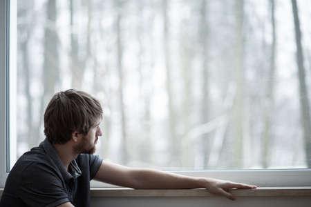 Junger Mann sitzt auf dem Boden des Wohnzimmers mit großem Fenster