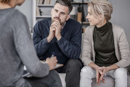 Wife and husband during marriage therapy with counselor