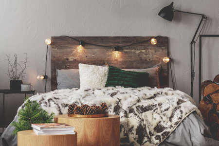 Christmas bedroom decor with lights, wood, spruce and cones