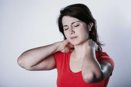 Frau mit Nacken- und Schulterschmerzen und -verletzungen, weibliche Hände an gelittenen Muskeln