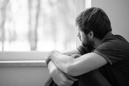 Sad young man sitting on the floor looking through the window