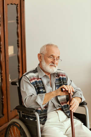 Elderly man sitting on a wheelchair and leaning on a stick