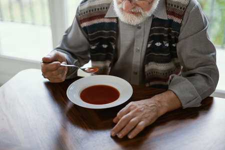 Close-up of older lonely man eating a soup in his home