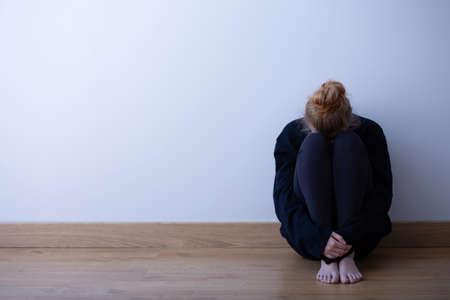 Trauriges Teenagermädchen, das zusammengerollt auf dem Boden sitzt, Kopienraum auf leerer Wand