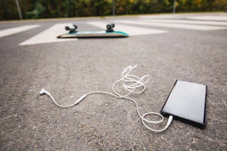 Phone on the street after skateboard accident Imagens