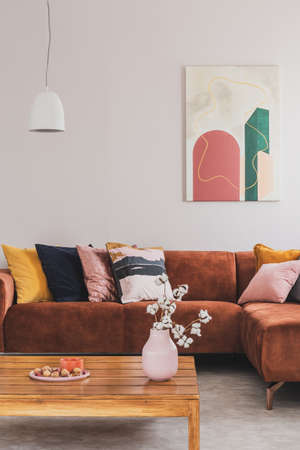 Real photo of a modern painting hanging above a brown, suede corner couch in elegant living room interior