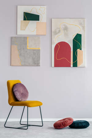 Real photo of a gray living room interior with a set of modern paintings on the wall and a velvet cushion on a yellow chair Imagens