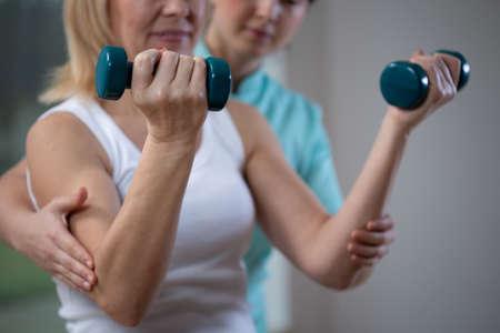 Fisioterapeuta profesional ayudando a la mujer mayor a levantar pesas de mano