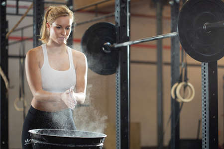 Beautiful blonde girl preparing to weightlifting at fitness center Reklamní fotografie